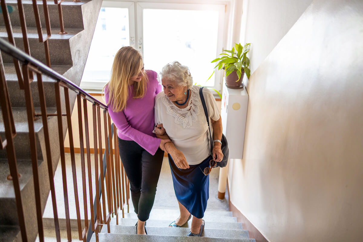 adult woman helping older woman up stairs_home safety tips for seniors