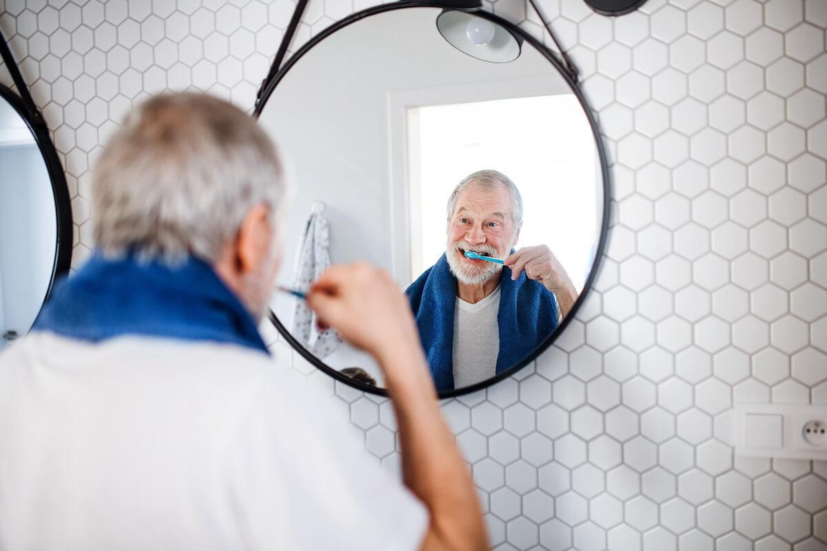 Senior Man brushing teeth importance of dental health