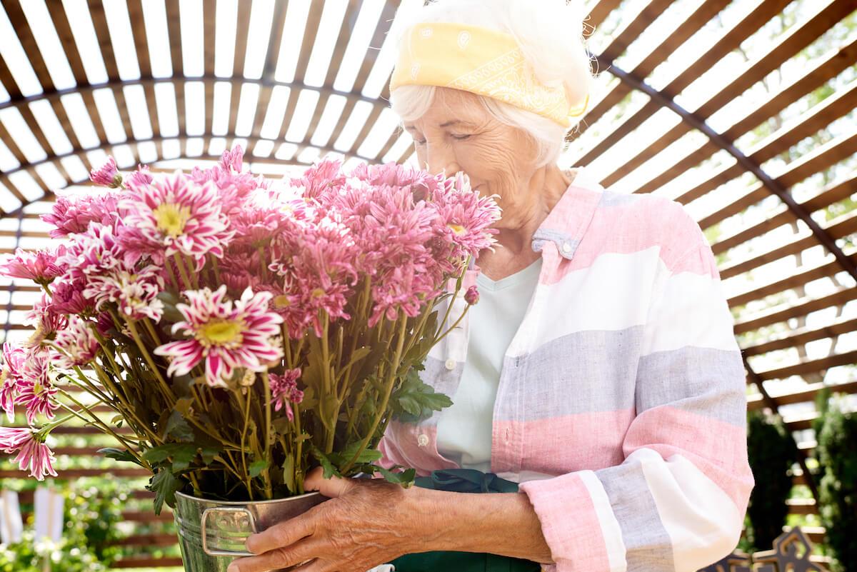 Senior woman smelling flowers_Managing Spring Allergies