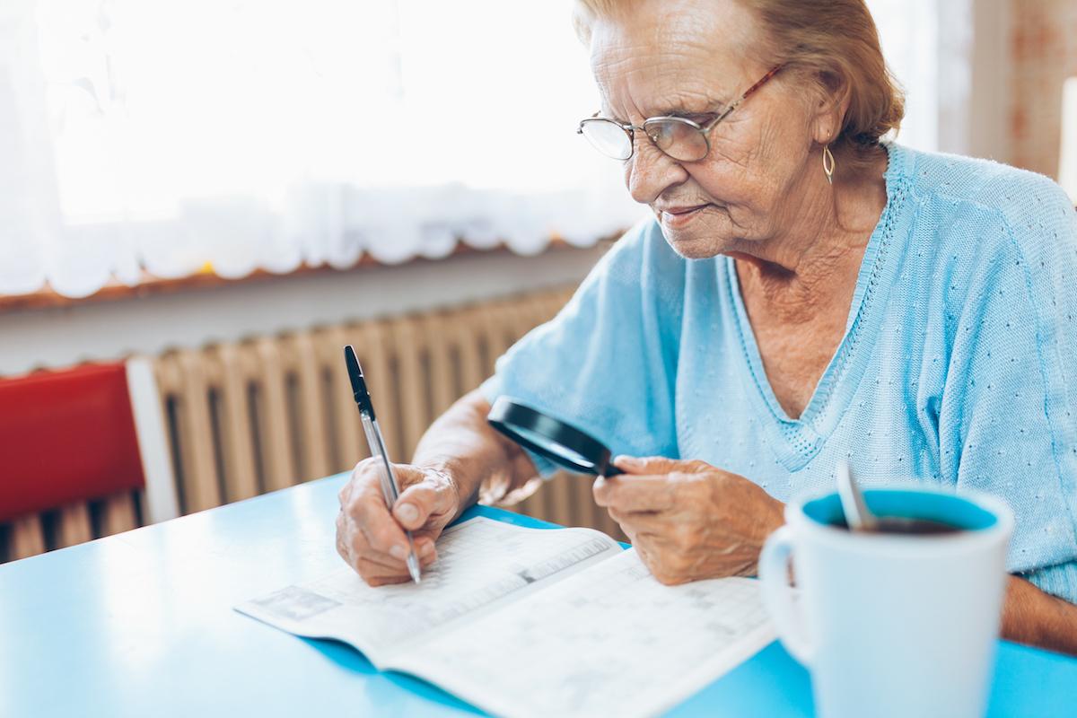 senior woman doing crossword puzzle_understanding parkinson's disease